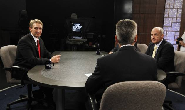 Rep. Jeff Flake, R-Ariz., left, and Democrat Richard Carmona, right, both listen to moderator Ted Simons, center, host and managing editor of Arizona Horizon at Eight, Arizona PBS, as he discusses the rules in the studio prior to an Arizona U.S. Senate debate Wednesday, Oct. 10, 2012, in Phoenix. The candidates are vying for the seat left open by retiring Sen. Jon Kyl, R-Ariz.(AP Photo/Ross D. Franklin)