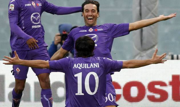 Fiorentina's Luca Toni, center, celebrates with teammates Alberto Aquilani, back to camera, and Juan Cuadrado, of Colombia, after scoring during a Serie A soccer match between Fiorentina and Atalanta at the Artemio Franchi stadium in Florence, Italy, Sunday Nov. 18, 2012. (AP Photo/Fabrizio Giovannozzi)