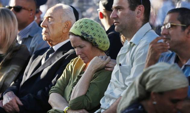 Rachel and Avi Fraenkel, parents of U.S.-Israeli national Naftali, 16, one of the three Israeli teens who were abducted and killed in the West Bank, mourn as they sit next to Israeli President Shimon Peres during their son'ss joint  funeral in the Israeli city of Modiin, Tuesday, July 1, 2014. Tens of thousands of mourners converged Tuesday in central Israel for the funeral service for three teenagers found dead in the West Bank after a two week search and crackdown on the Hamas militant group, which Israeli leaders have accused of abducting and killing the young men. The deaths of Eyal Yifrah, 19, Gilad Shaar, 16, and Naftali Fraenkel, a 16-year-old with dual Israeli-American citizenship, have prompted angry calls for revenge and Prime Minister Benjamin Netanyahu convened his security Cabinet for an emergency meeting to discuss a response to the killings, hours after airstrikes targeted dozens of suspected Hamas positions in the Gaza Strip.(AP Photo/Baz Ratner, Pool)