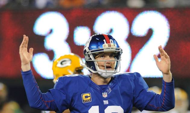 New York Giants quarterback Eli Manning (10) signals a touchdown during the second half of an NFL football game, Sunday, Nov. 25, 2012 in East Rutherford, N.J. After further review Manning's pass to Hakeem Nicks was ruled a touchdown. (AP Photo/Bill Kostroun)