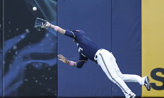 Milwaukee Brewers' Corey Hart makes a diving catch on a ball hit by Chicago Cubs' Starlin Castro during the sixth inning of a baseball game on Sunday, May 13, 2012, in Milwaukee. (AP Photo/Jeffrey Phelps)