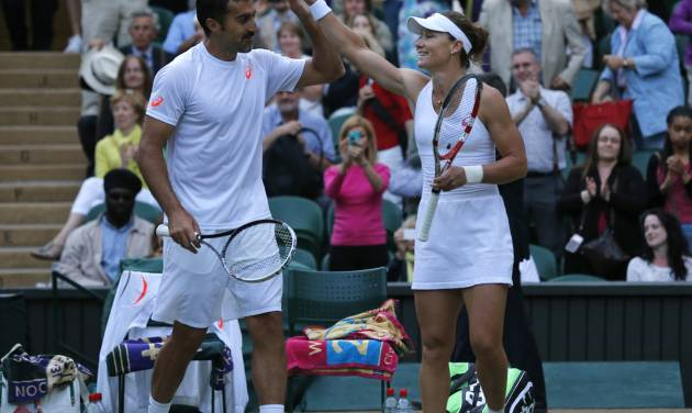 Nenad Zimonjic of Serbia and Samantha Stosur of Australia, right, celebrate a point during the mixed doubles final against Max Mirnyi of Belarus and Hao-Ching Chan of Taiwan at the All England Lawn Tennis Championships in Wimbledon, London, Sunday July 6, 2014. (AP Photo/Ben Curtis)