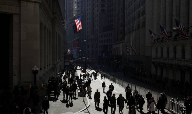 FILE - In this Wednesday, Nov. 2, 2011, file photo, people walk in front of the New York Stock Exchange, in New York. The Dow reaches its highest record ever on Tuesday, March 5, 2013. Yet the market's run-up feels worlds away from the lives of many Americans. Wages have only recently started to recover after months of declines that stretched family budgets thin. Unemployment is stuck near 8 percent, high enough that most Americans still know people who are out of work. Signs of a housing recovery have boosted stocks, yet millions of people face foreclosure. (AP Photo/Seth Wenig, File)