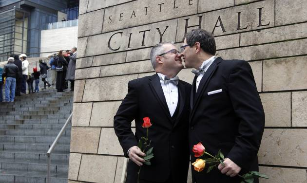 Terry Gilbert, left, kisses his husband Paul Beppler after wedding at Seattle City Hall, becoming among the first gay couples to legally wed in the state, Sunday, Dec. 9, 2012, in Seattle. Gov. Chris Gregoire signed a voter-approved law legalizing gay marriage Dec. 5 and weddings for gay and lesbian couples began in Washington on Sunday, following the three-day waiting period after marriage licenses were issued earlier in the week. (AP Photo/Elaine Thompson)