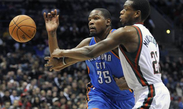 Oklahoma City Thunder's Kevin Durant (35) and Milwaukee Bucks' Khris Middleton scramble for a loose ball during the first half of an NBA basketball game Saturday, Nov. 16, 2013, in Milwaukee. (AP Photo/Jim Prisching)