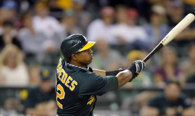 Oakland Athletics' Yoenis Cespedes hits a sacrifice fly to score a run against the Seattle Mariners during the ninth inning of a baseball game in Seattle on Saturday, Sept. 8, 2012. The Athletics won 6-1. (AP Photo/John Froschauer)