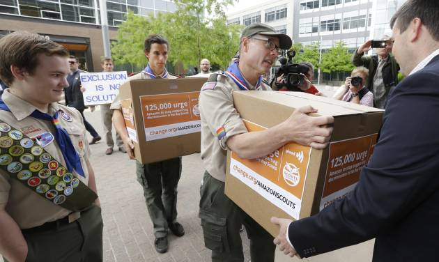 Geoffrey McGrath, center, a gay Boy Scout troop leader and Eagle Scout from Seattle, who had his membership in the Scouts revoked by the organization earlier this year, hands Amazon.com security worker Matt Oien, right, a box, Wednesday, May 21, 2014, at Amazon headquarters in Seattle that was one of four containing signatures and comments on a petition to Amazon.com urging the company to stop donating money to the Boy Scouts due to the organization's policy of excluding openly gay adults from leadership positions, despite recently accepting gay youth as scouts. The petition was started by Pascal Tessier, 17, left, a gay Eagle Scout from Kensington, Md. (AP Photo/Ted S. Warren)