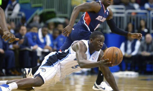 Orlando Magic shooting guard Victor Oladipo (5) passes to a teammate after gaining control of a loose ball in front of Atlanta Hawks point guard Shelvin Mack during the first half of an NBA basketball game in Orlando, Fla., Wednesday, Jan. 22, 2014. (AP Photo/Phelan M. Ebenhack)