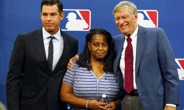Former major league outfielder Billy Bean, left, Lutha Burke and Baseball Commissioner Bud Selig, right, pose for a photo after a news conference at baseball's All-Star game, Tuesday, July 15, 2014, in Minneapolis. Major League Baseball has appointed Bean, who came out as gay after his playing career, to serve as a consultant in guiding the sport toward greater inclusion and equality. Burke is the sister of Glenn Burke, who was the first MLB player to come out as gay after retiring. Burke died in 1995. (AP Photo/Paul Sancya)