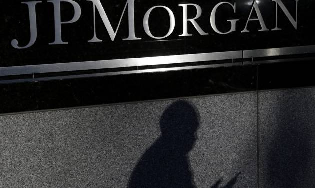 FILE - In this Nov. 19, 2013, file photo, the shadows of a pedestrian is cast under a sign in front of JPMorgan Chase & Co. headquarters in New York. JPMorgan reports quarterly financial results on Tuesday, July 15, 2014. (AP Photo/Seth Wenig, File)