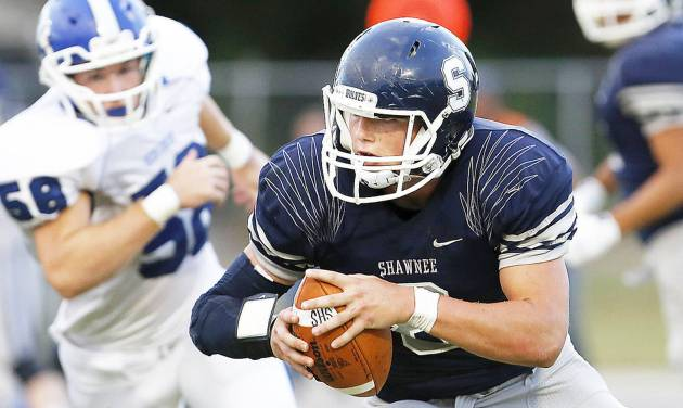 Shawnee quarterback John Jacobs scrambles in the first quarter as he is chased by Deer Creek defensive end Daniel Smith during Friday's game at Harris Stadium in Shawnee.  Photo by Jim Beckel The Oklahoman.