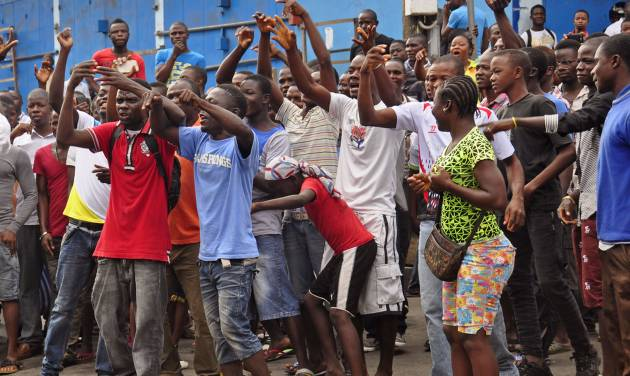 Residents from an area close to the West Point Ebola center, protest as they are not allowed to enter the area leading to their homes, after Liberia security forces blocked roads, as the government clamps down on the movement of people to prevent the spread of the Ebola virus in the city of Monrovia, Liberia, Wednesday, Aug. 20, 2014. Security forces deployed Wednesday to enforce a quarantine around a slum in the Liberian capital, stepping up the government's fight to stop the spread of Ebola and unnerving residents.(AP Photo/Abbas Dulleh)