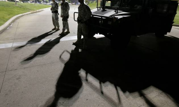 FILE - This Aug. 18, 2014 file photo shows members of the Missouri National Guard standing watch outside a command post near a protest for Michael Brown, who was killed by a police officer Aug. 9 in Ferguson, Mo. Brown's shooting has sparked more than a week of protests, riots and looting in the St. Louis suburb. Eric Holder, who is leading the federal response to the racial turmoil in Ferguson, Missouri, talks about the nation's civil rights struggles in a way none of the 81 previous U.S. attorneys general could _ by telling his own family story. (AP Photo/Charlie Riedel, File)
