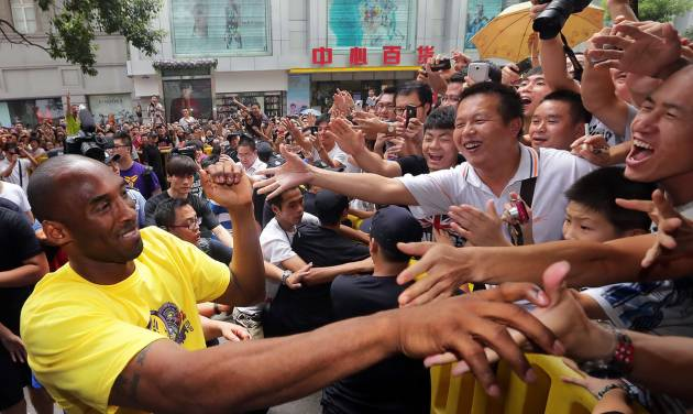 """FILE - In this Aug. 16, 2012 file photo, Los Angeles Lakers' Kobe Bryant, left, shakes hands with Chinese fans during a """"meet the fans"""" event in Wuhan in central China's Hubei province. He has not uttered one word yet, Bryant's mere presence on a Twitter-like Chinese-language site has stirred plenty of excitement. Sina Weibo has verified that the NBA superstar has set up an individual account on its hugely popular microblogging site. Bryant's followers numbered more than 100,000 within hours on Thursday, Feb. 14, 2013, although no comments from Bryant had appeared. (AP Photo) CHINA OUT"""