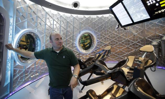 Garrett Reisman, program lead for crew vehicles of the SpaceX, stands inside the SpaceX Dragon V2 at the headquarters on Thursday, May 29, 2014, in Hawthorne, Calif. SpaceX, which has flown unmanned cargo capsules to the International Space Station, unveiled the new spacecraft Thursday designed to ferry astronauts to low-Earth orbit. (AP Photo/Jae C. Hong)