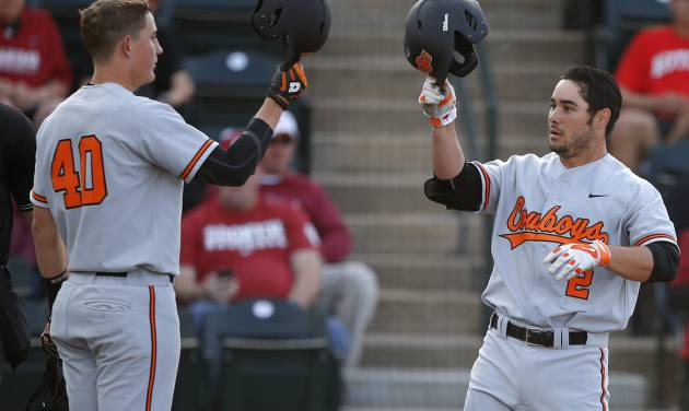 OSU's Tim Arakawa, right, celebrates with Craig McConaughy after hitting a home run during the Bedlam baseball game between the University of Oklahoma and Oklahoma State University at L. Dale Mitchell Park in Norman, Okla., Tuesday, April 1, 2014. Oklahoma State won 3-1. Photo by Bryan Terry, The Oklahoman