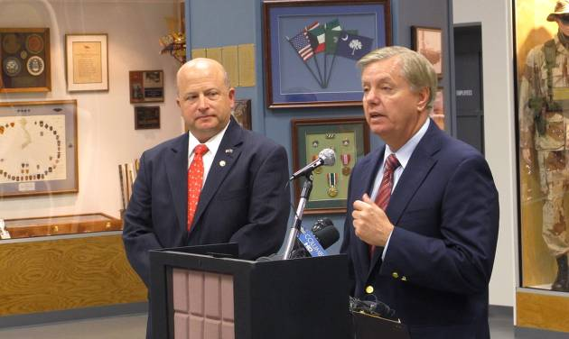 South Carolina Adjutant General Robert Livingston, left, listens as U.S. Sen. Lindsey Graham, right, talks about a bill passed by Congress to improve health care for veterans on Tuesday, Aug. 5, 2014, in Columbia, S.C. Graham said the most important part of the bill is the ability to fire poorly performing employees. (AP Photo/Jeffrey Collins)