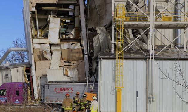 Firefighters stage outside the International Nutrition plant in Omaha, Neb., Monday, where a fire and explosion took place Jan. 20, 2014. At least nine people have been hospitalized and others could be trapped at the animal feed processing plant. (AP Photo/Nati Harnik)