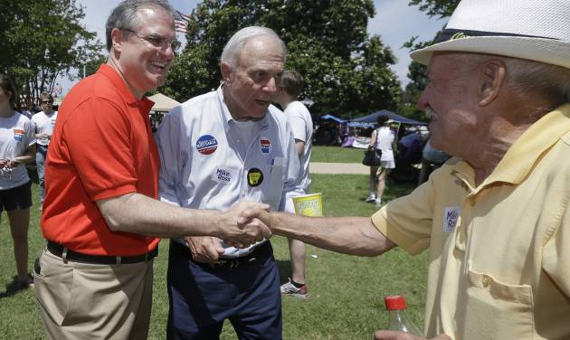 FILE - In this file photo taken June 14, 2014, Democratic U.S. Sen. Mark Pryor, left, campaigns for re-election with his father, former U.S. Sen. David Pryor, D-Ark., center, in Warren, Ark. Mark Pryor is reaching into his own medical history to explain his vote on the nation's new health care law, telling Arkansans that his battle with a rare cancer 18 years ago influenced his vote. (AP Photo/Danny Johnston, File)
