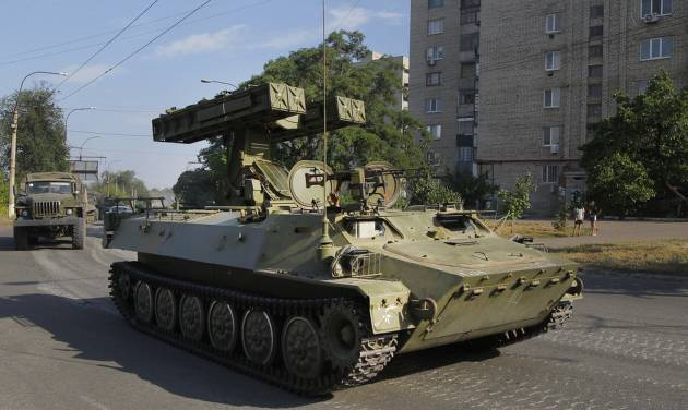 A Pro-Russian missile launcher drives in the town of Krasnodon, eastern Ukraine, Sunday, Aug. 17, 2014. A column of several dozen heavy vehicles, including tanks and at least one rocket launcher, rolled through rebel-held territory on Sunday.(AP Photo/Sergei Grits)