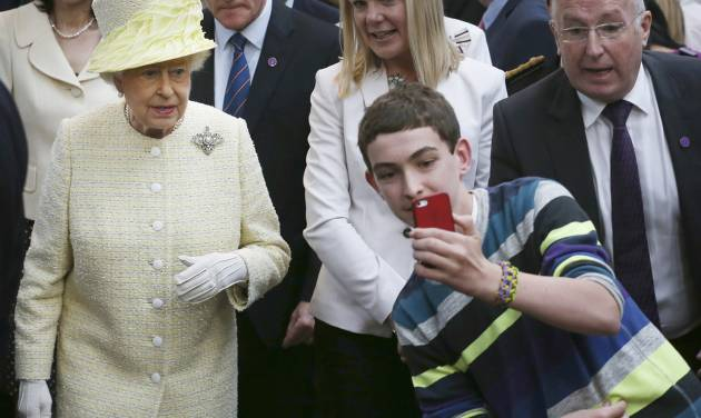 A local youth takes a selfie photograph in front of Queen Elizabeth II during a visit to St George's indoor market on  in Belfast Tuesday June 24, 2014. The Queen is on a 3 day visit to Northern Ireland .  (AP Photo/Peter Macdiarmid, Pool)