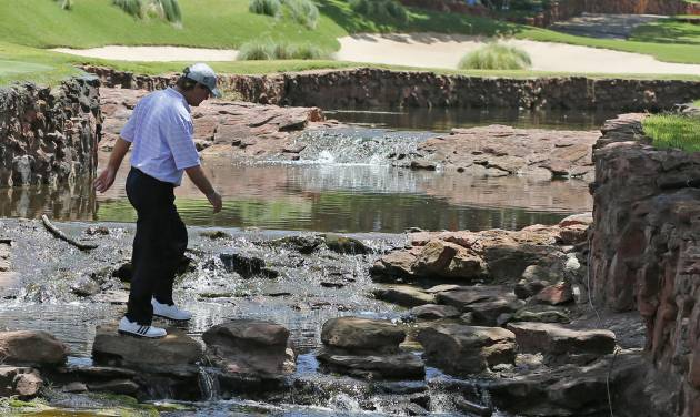 Gene Sauers walks across a creek to the fifth tee during the final round of the U.S. Senior Open golf tournament at Oak Tree National in Edmond, Okla., Sunday, July 13, 2014. (AP Photo/Sue Ogrocki)