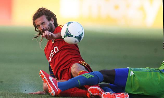 Real Salt Lake midfielder Kyle Beckerman, left, collides with Seattle Sounders FC defender Djimi Traore during the first half of an MLS soccer game at Rio Tinto Stadium in Sandy, Utah, on Saturday, June 22, 2013. (AP Photo/The Salt Lake Tribune, Kim Raff)  DESERET NEWS OUT; LOCAL TV OUT; MAGS OUT.