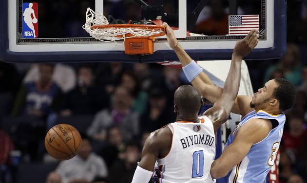 Denver Nuggets' JaVale McGee (34) dunks over Charlotte Bobcats' Bismack Biyombo (0) during the first half of an NBA basketball game in Charlotte, N.C., Saturday, Feb. 23, 2013. (AP Photo/Bob Leverone)