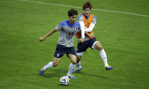 South Korea's Park Chu-young, left, and Kim Young-gwon fight for the ball during a training session in Foz do Iguacu, Brazil, Thursday, June 12, 2014. South Korea play in group H of the 2014 soccer World Cup. (AP Photo/Lee Jin-man)