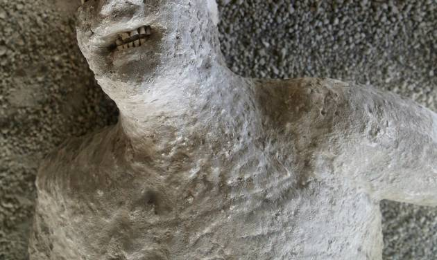In this May 14, 2014 photo, a plaster cast captures the horror of a victim of the volcanic eruption of Mount Vesuvius, which in A.D. 79 destroyed the ancient town of Pompeii, near modern-day Naples, Italy. The plaster injection process was devised by 19th-century archaeologist Giuseppi Fiorelli to create casts of bodies encased by volcanic ash. An estimated 2.5 million people visit the ruins each year. (AP Photo/Michelle Locke)
