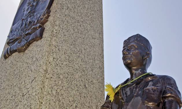 """FILE - In this Sept. 1, 2005 file photo, a single flower adorns the neck of one of the bronze miners on the monument at the grave of Mary """"Mother"""" Jones in the Union Miners Cemetary in Mount Olive, Ill. Mother Jones, a champion of organized labor from the 1870's to her death in 1930, is revered in the small Illinois town. The Illinois monument to the famed labor crusader is getting a makeover, thanks to donors in 17 states. Restoration of the monument is to be complete by bid-2015. (AP photo/Tom Gannam, File)"""