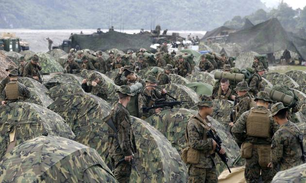 FILE - In this Oct. 9, 2012 file photo, U.S. Marines fix their tents as they arrive at Crow Valley, Tarlac province in northern Philippines, to take part in the joint U.S.-Philippines amphibious landing exercise, dubbed PHIBLEX 2013. Filipino officials and a confidential government document say that the United States and the Philippines on Sunday, April 27, 2014 reached a 10-year pact that will allow a larger American military presence in the country. It will give U.S. troops temporary access to local military camps where they can preposition fighter jets and warships. (AP Photo/Bullit Marquez, File)