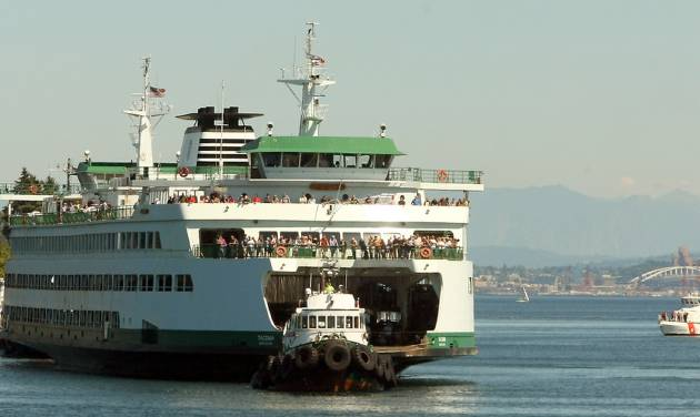 Tugboats bring the M/V Tacoma to dock after it lost power while traveling from Seattle to Bainbridge Island, Washington on Tuesday, July 29, 2014. (AP Photo/Kitsap Sun, Meegan M. Reid)