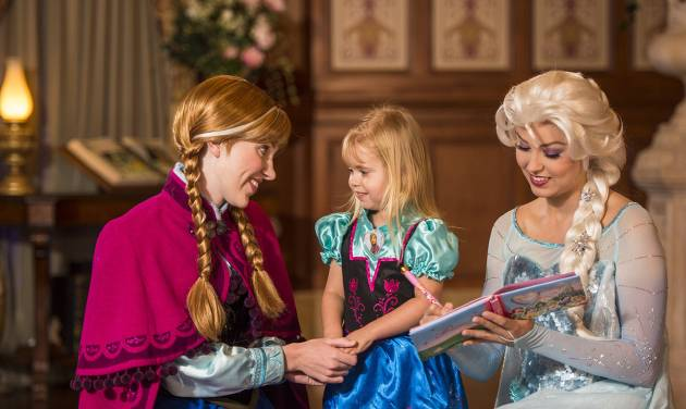 "This undated image released by Disney shows Disney characters Anna, left, and her sister Elsa, right, from the animated film ""Frozen"" at Princess Fairytale Hall with a young fan at a meet-and-greet at Walt Disney World Resort in Lake Buena Vista, Fla. Wait times to meet the sisters stretches for hours and reservations are snapped up as soon as they become available, part of a frenzy for all things ""Frozen.""  (AP Photo/Disney, Matt Stroshane)"