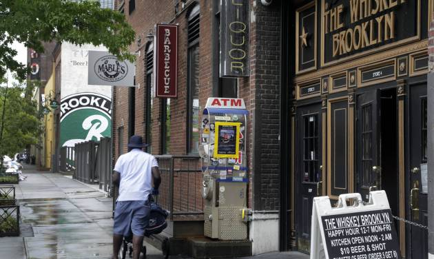 In this July 1, 2013 photo, restaurants line the street adjacent to the Brooklyn Brewery, in the Williamsburg section of the Brooklyn borough of New York. In rundown urban neighborhoods across the country, craft breweries helped transform the neighborhoods around them, drawing young new residents and other small businesses. (AP Photo/Richard Drew)