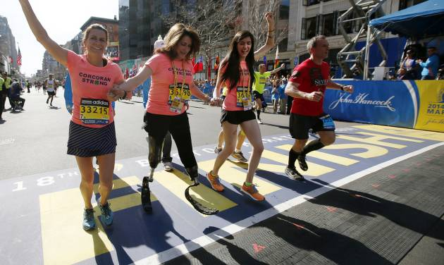 Double amputee Celeste Corcoran, center, a victim of last year's bombings, reaches the finish line of the 118th Boston Marathon, Monday, April 21, 2014, in Boston, with the aid her sister Carmen Acabbo, left, and daughter Sydney, right, who was also wounded last year. (AP Photo/Elise Amendola)