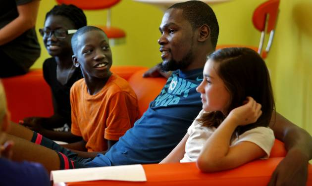 Boubacar Diahe reacts as Kevin Durant surprises youngsters from the Bethany YMCA Summer Camp at the Orange Leaf Yogurt shop on Tuesday, July 14, 2015 in Moore, Okla. At left is N'Diasse Diahe and Lana Daniels is at right. Earlier, the youngsters submitted ideas on how to make their community better. Photo by Steve Sisney, The Oklahoman