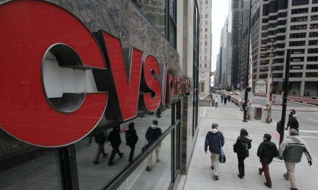 FILE- In this Feb 7, 2012 file photo, pedestrians walk pass a CVS store in Chicago. CVS Caremark Corp. said Tuesday, Nov. 6, 2012, that its third-quarter earnings climbed 16 percent. The drugstore operator and pharmacy benefits manager posted revenue increases in both businesses, benefiting from new customers won from rivals, and raised its full-year earnings outlook. (AP Photo/M. Spencer Green, File)