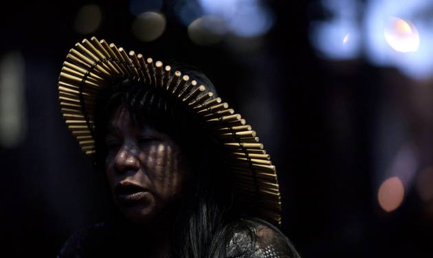 "An indigenous woman participates in a protest at a building known as the ""Old Indian Museum,"" located near the Maracana stadium in Rio de Janeiro, Brazil, during the United Nations Conference on Sustainable Development, or Rio+20, Thursday June 21, 2012. Indigenous people who have built homes at the building will be relocated due to works on the stadium and the surrounding area as part of Brazil's preparations for the 2014 World Cup. (AP Photo/Felipe Dana)"
