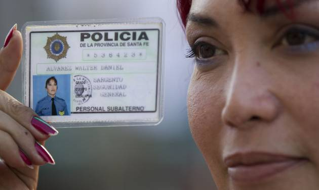 Transsexual Daniel Walter Alvarez shows his police credential outside Congress in Buenos Aires, Argentina, Wednesday, May 9, 2012. Argentina's Congress is set to approve on Wednesday the Gender Identity Law, which allows citizens to change their gender in public records, including birth certificates and national identity cards. (AP Photo/Natacha Pisarenko)