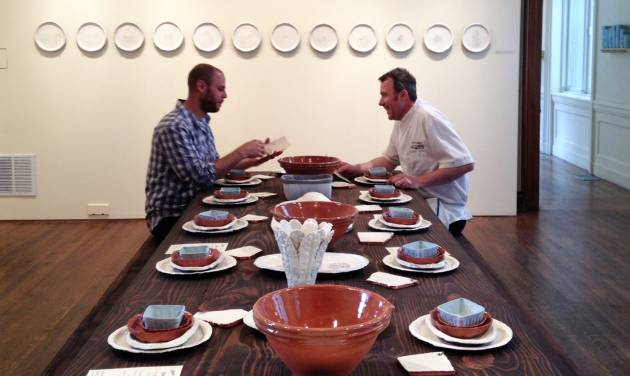 "This 2014 photo provided by the Philadelphia Art Alliance shows artist Gregg Moore, left, and chef  Pierre Calmels at a table set with Moore's fine ceramic pottery for a show called ""Heirloom,""  in Philadelphia. Calmels serves a seven-course, $150 dinner called ""Table d'Hote"" at the museum using Moore's pottery. Moore says the art, which is  part of a movement called social practice art, is created by the experience of the food, ceramics, museum space and the people sharing the meal.  (AP Photo/Philadelphia Art Alliance, Sarah Archer)"