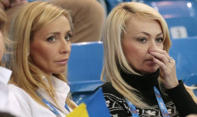 FILE - In this Saturday, Feb. 8, 2014 file photo, Yana Rudkovskaya, right, the wife of Russian figure skater Evgeni Plushenko, watches the team ice dance short dance figure skating competition with retired figure skater Tatiana Navka of Belarus at the Iceberg Skating Palace during the 2014 Winter Olympics in Sochi, Russia. In Russia, Plushenko is practically royalty, and being his wife has its benefits. (AP Photo/Ivan Sekretarev, File)