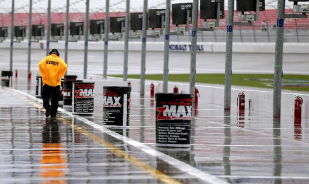 A track security guard walks along pit road during a rain delay before practice for the NASCAR Nationwide and Sprint Cup Series auto race, Friday, March 8, 2013 in Las Vegas. (AP Photo/Julie Jacobson)