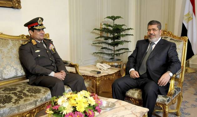 "FILE - In this Thursday Feb, 21, 2013 file photo, released by the Egyptian Presidency, Egyptian Minister of Defense, Lt. Gen. Abdel-Fattah el-Sissi, left, meets with Egyptian President Mohammed Morsi at the presidential headquarters in Cairo, Egypt. El-Sissi has warned that the military is ready to intervene to stop the nation from entering a ""dark tunnel"" of internal conflict. (AP Photo/Mohammed Abd El Moaty, Egyptian Presidency, File)"