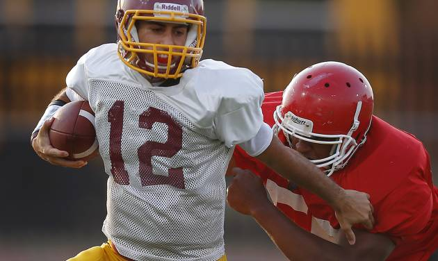 HIGH SCHOOL FOOTBALL: Putnam City North's John Simon fights off Lawton's BJ Scott during a football scrimmage at Putnam City High School in Warr Acres, Okla., Thursday, August 16, 2012. Photo by Bryan Terry, The Oklahoman