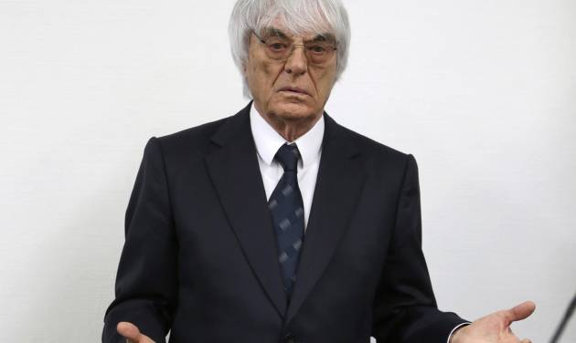 Formula One boss Bernie Ecclestone gestures as he arrives for his trial in the regional court in Munich, southern Germany, Tuesday, Aug. 5, 2014. German prosecutors said Tuesday that they will accept dropping the bribery case against Ecclestone in exchange for a US dollar 100 million payment by the Formula One boss, and judges were considering whether to close his trial. Ecclestone went on trial at the Munich state court in late April on charges of bribery and incitement to breach of trust — which could, if he were convicted, carry a sentence of up to 10 years in prison. (AP Photo/Matthias Schrader)
