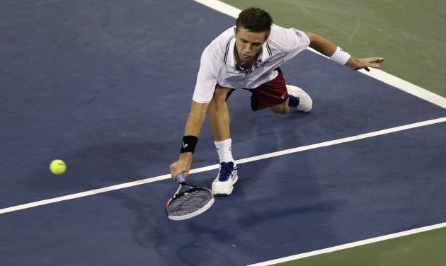 Tim Smyczek, of the United States, stretches on a return to Marcel Granollers, of Spain, during the third round of the 2013 U.S. Open tennis tournament, Sunday, Sept. 1, 2013, in New York. (AP Photo/Charles Krupa)