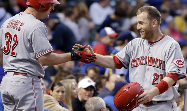 Cincinnati Reds' Todd Frazier, right, celebrates with Jay Bruce after scoring on a double hit by Joey Votto during the sixth inning of a baseball game against the Chicago Cubs in Chicago, Wednesday, June 25, 2014. (AP Photo/Nam Y. Huh)