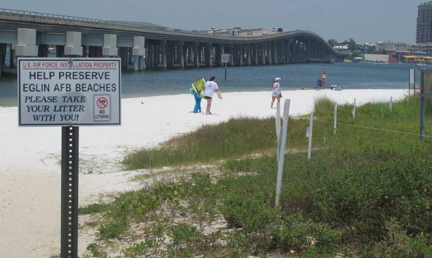 In this July 7, 2014 photo, people look for a place to set up on a shallow beach under a highway bridge in Destin, Fla. The beach is under the controlled of Eglin Air Force Base where it is occasionally used to practice amphibious landings and test high-tech weapons. The public is welcome to use the beach. (AP Photo/Melissa Nelson-Gabriel)