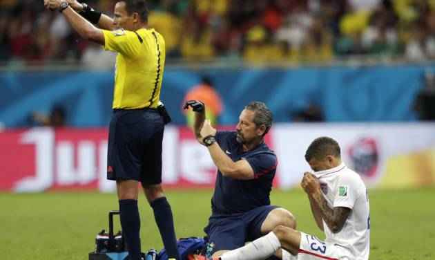 United States' Fabian Johnson, right, receives treatment during the World Cup round of 16 soccer match between Belgium and the USA at the Arena Fonte Nova in Salvador, Brazil, Tuesday, July 1, 2014. (AP Photo/Julio Cortez)